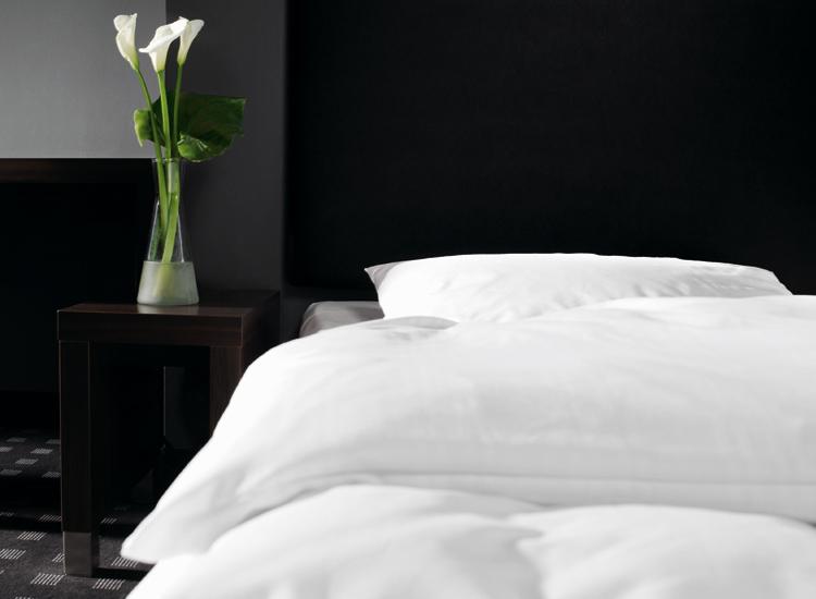 Zimmermaedchen steht neben frisch gemachtem Bett